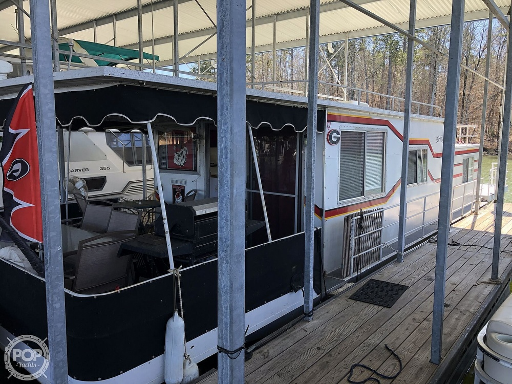 Features Covered Bow Deck With Furniture And Gas Grill